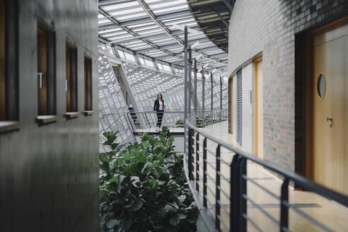 Businesswoman standing on a skywalk in modern office building - JOSF04155