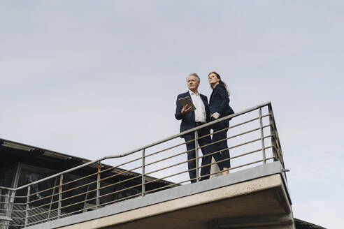 Businessman and businesswoman standing on a balcony outside office building - JOSF04179