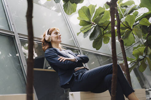 Businesswoman having a break in a modern office building - JOSF04182