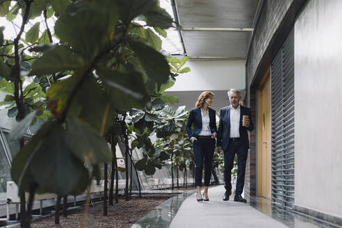 Businessman and businesswoman walking and talking in modern office building - JOSF04185