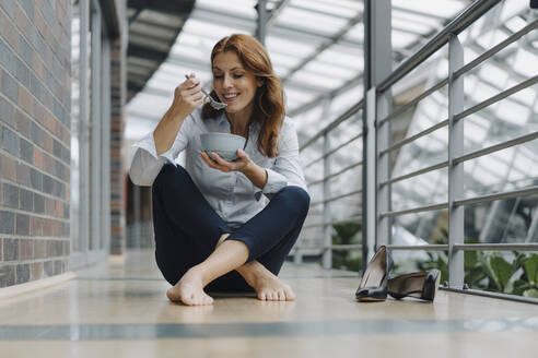 Businesswoman sitting on the floor in office eating muesli - JOSF04191