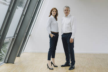 Portrait of confident businessman and businesswoman standing in office - JOSF04197