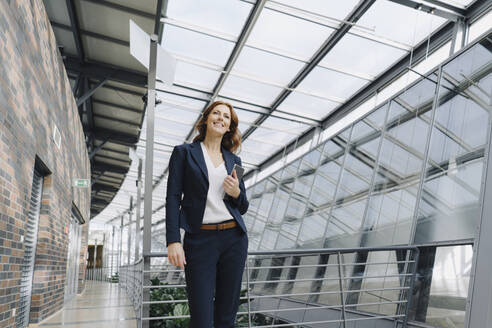 Smiling businesswoman holding a tablet in a modern office building - JOSF04200