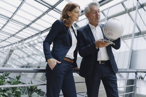 Businessman and businesswoman looking at globe in modern office building - JOSF04203