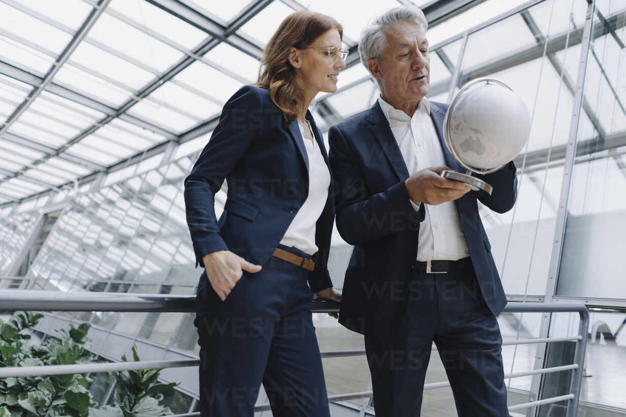 Businessman and businesswoman looking at globe in modern office building - JOSF04203 - Joseffson/Westend61