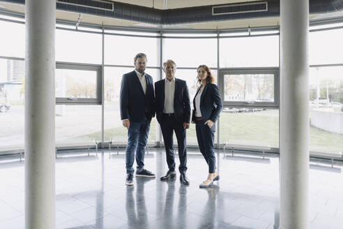Portrait of confident business people standing in modern office building - JOSF04209