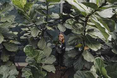 Businesswoman listening to music surrounded by large plants - JOSF04215