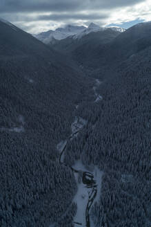 Aerial view of river by trees on mountains against cloudy sky during winter - CAVF72489