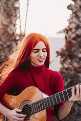 Portrait of redheaded young woman playing guitar on the beach, Almunecar, Spain - LJF01214
