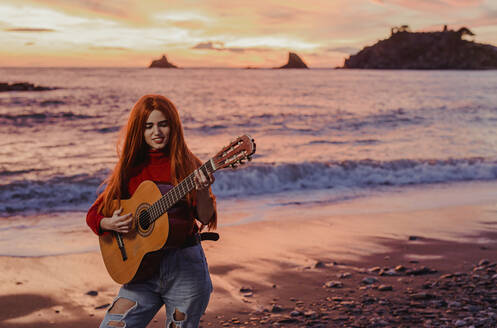 Portrait of redheaded young woman playing guitar on the beach at sunset, Almunecar, Spain - LJF01217
