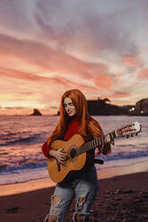Portrait of redheaded young woman playing guitar on the beach at sunset, Almunecar, Spain - LJF01220