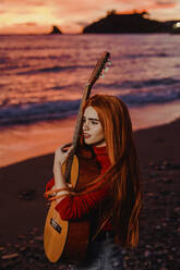 Portrait of redheaded young woman with guitar on the beach at sunset looking at distance, Almunecar, Spain - LJF01223