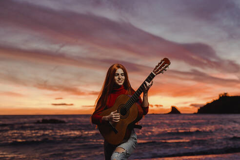Portrait of redheaded young woman playing guitar on the beach at sunset, Almunecar, Spain - LJF01226