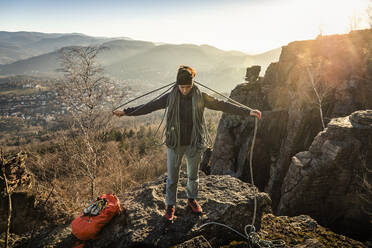Female climber with rope standing on Battert rock at sunset, Baden-Baden, Germany - MSUF00109