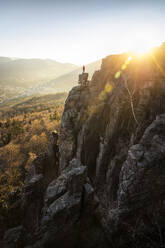Man standing on rock needle at sunset at Battert rock, Baden-Baden, Germany - MSUF00112