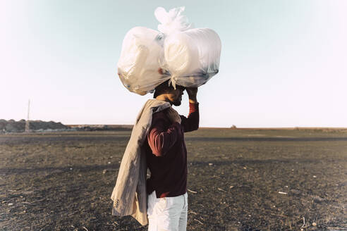 Young man carrying bag with plastic bottles on his head in barren land - ERRF02486