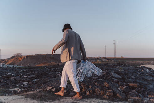 Young man holding empty plastic bottles walking in barren land - ERRF02495
