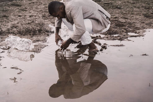 Young man filling plastic bottle with water at a water hole - ERRF02504
