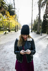 Beautiful blond woman using her smartphone in a park - MGOF04230