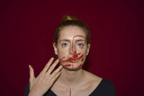 Portrait of young woman smearing paint on her face - AFVF04804