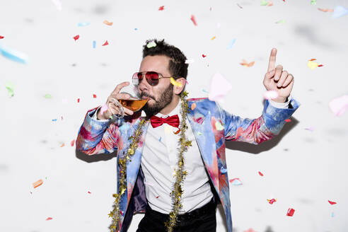 Cool and stylish man wearing a colorful suit and sunglasses celebrating a party with confetti and drinking - LOTF00087
