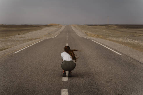 Back view of woman crouching on median strip of empty country road, Fez, Morocco - AFVF04823