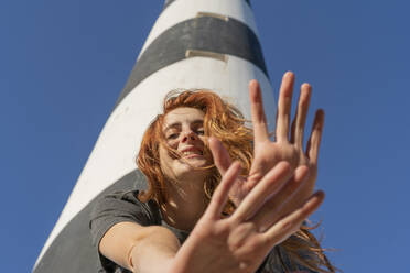 Portrait of happy redheaded young woman at a lighthouse - AFVF04851