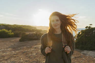 Portrait of redheaded young woman at the coast at sunset, Ibiza, Spain - AFVF04857