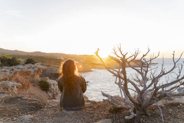 Redheaded young woman sitting at the coast at sunset, Ibiza, Spain - AFVF04863