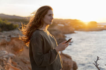 Redheaded young woman with cell phone at the coast at sunset, Ibiza, Spain - AFVF04866