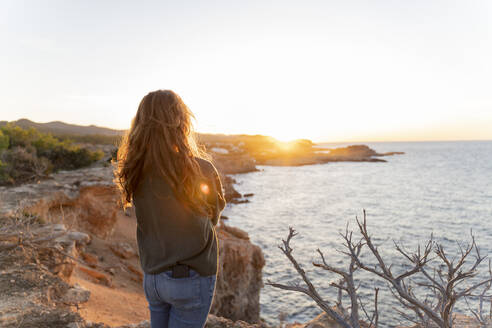 Redheaded young woman standing at the coast at sunset, Ibiza, Spain - AFVF04869