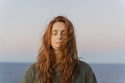 Redheaded young woman with closed eyes at the coast at sunset, Ibiza, Spain - AFVF04872