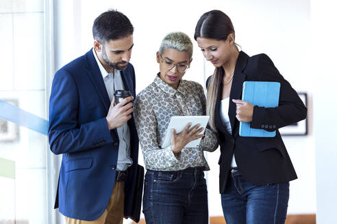Business people sharing tablet in office - JSRF00764
