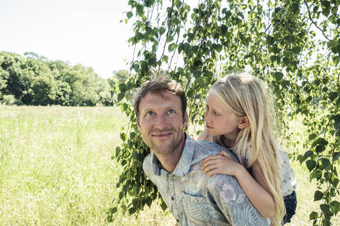 Father carrying daughter piggyback under a birch tree - WFF00224