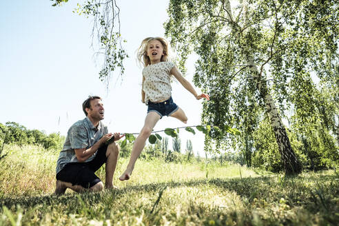 Father with daughter jumping over stick in poppy meadow - WFF00245
