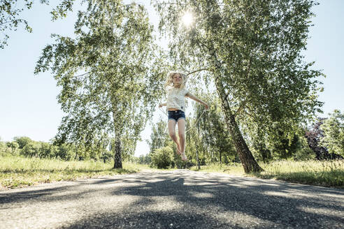 Happy girl skipping rope on a park path - WFF00251