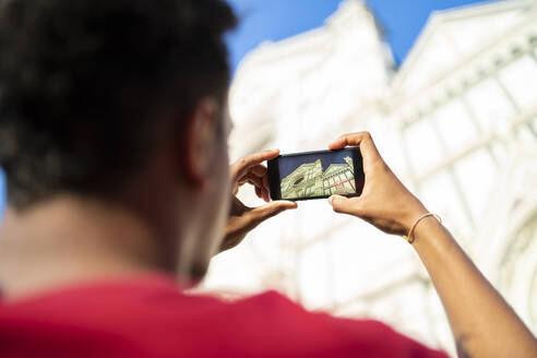 Young man taking a smartphone picture of Basilica di Santa Maria del Fiore, Florence, Italy - FBAF01140