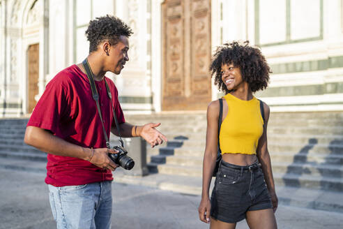 Happy young tourist couple walking and talking in the city, Florence, Italy - FBAF01149