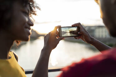 Young tourist couple taking a picture on a bridge above river Arno at sunset, Florence, Italy - FBAF01167