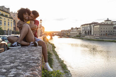 Affectionate young tourist couple sitting on a wall at river Arno at sunset, Florence, Italy - FBAF01170