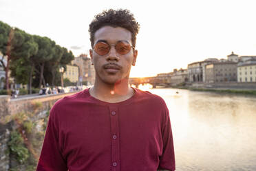 Portrait of young man at river Arno at sunset, Florence, Italy - FBAF01179