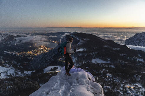 Mountaineer on the mountain summit during twilight, Orobie Alps, Lecco, Italy - MCVF00173