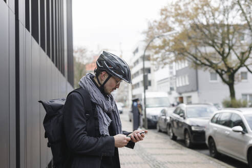 Young man with cycling helmet and backpack standing on pavement looking at cell phone - KMKF01154