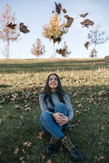 Portrait of happy teenage girl sitting on a meadow watching tumbling autumn leaves - GRCF00008