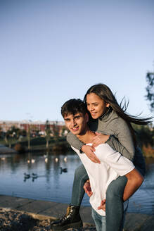 Portrait of happy teenage boy giving his girlfriend a piggyback ride - GRCF00011