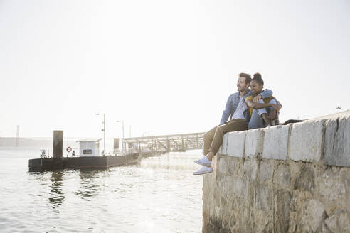 Young couple sitting on pier at the waterfront enjoying the view, Lisbon, Portugal - UUF19812