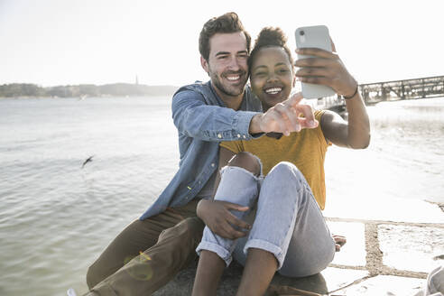 Happy young couple sitting on pier at the waterfront taking a selfie, Lisbon, Portugal - UUF19818