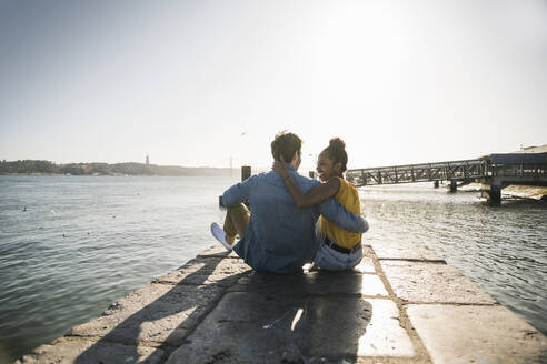Rear view of young couple sitting on pier at the waterfront, Lisbon, Portugal - UUF19821