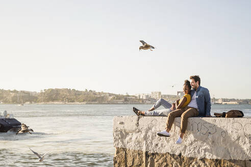Young couple sitting on pier at the waterfront enjoying the view, Lisbon, Portugal - UUF19845