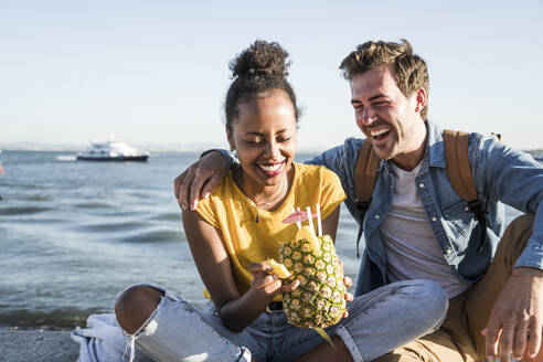 Happy young couple sitting on pier at the waterfront with a pineapple, Lisbon, Portugal - UUF19851